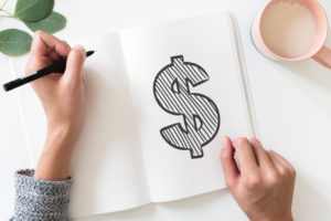 Person drawing money sign in notebook