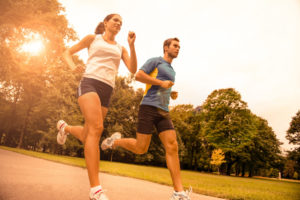 Man and woman  jogging outdoors in the park.